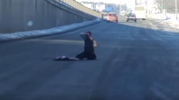 В Киеве водителей напугала женщина, которая ползала и срывала с себя одежду